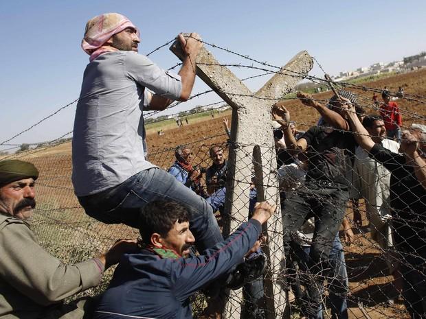 Curdos turcos e sírios derrubam parte de cerca na fronteira entre os dois países, perto da cidade de Suruc, na Turquia. Desde o início do ataque do Estado Islâmico iniciou à cidade de Kobani, na Síria, mais de 140 mil curdos já cruzaram a fronteira (Foto: Murad Sezer/Reuters)