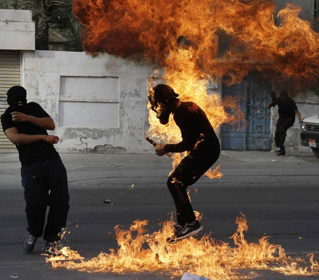 manifestante segurada bomba caseira feita com gasolina (Foto: Hasan Jamali/AP)