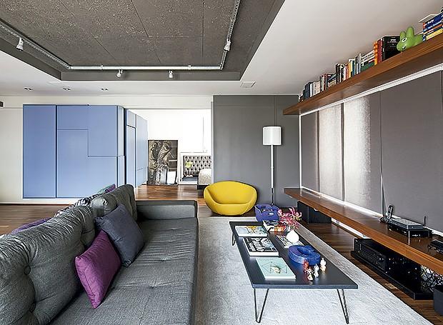 O banco de madeira acompanha toda a extensão da parede e vira assento extra na sala (Foto: Maíra Acayaba/ Editora Globo)