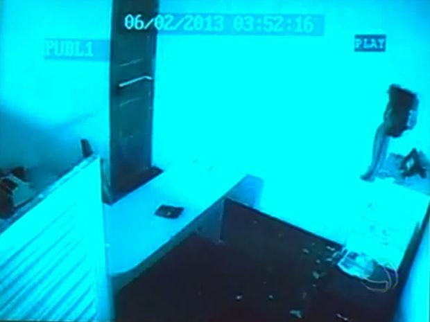Imagens mostram  momento em assaltante faz buraco em parede e, com o braço, tenta abrir cofres. (Foto: Reprodução/TVCA)