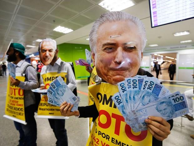 Ativistas usam máscaras do presidente Michel Temer e placas de 'Compro voto', distribuindo 'emendas orçamentárias' e dinheiro falso a deputados que voltavam do recesso parlamentar na área de desembarque do Aeroporto de Brasília. Na ocasião, o grupo de ati