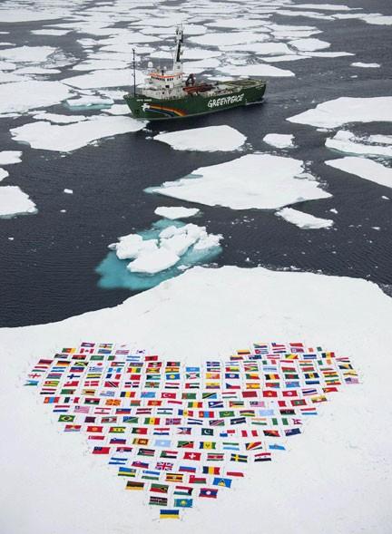 Bandeiras dos 193 países que integram a ONU são vistas na neve em frente ao navio My Arctic Sunrise, do Greenpeace, em foto do dia 14 divulgada nesta quarta (19). A organização aproveitou a viagem para apelar à ONU por medidas contra o degelo do Ártico. (Foto: AFP/Danile Beltra/Greenpeace)