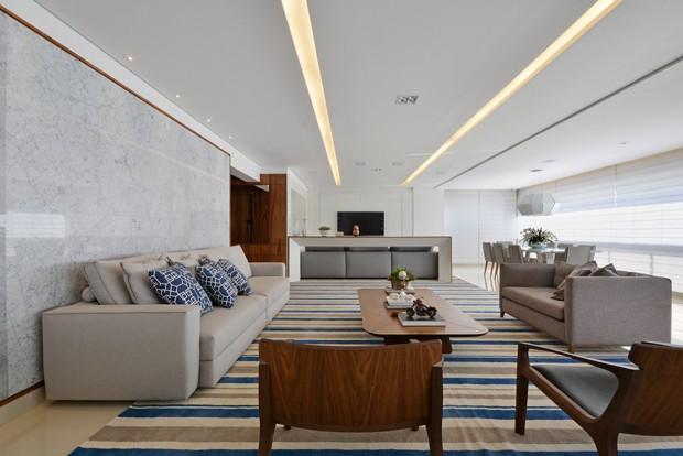sala-estar-poltronas-madeira-tapete-listras-azuis-parede-marmore-branco (Foto: Marcus Camargo/Divulgação)