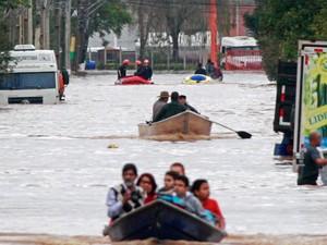 Moradores de Esteio, no Rio Grande do sul, usam canoas durante enchente na cidade. Diversas famílias tiveram que abandonar suas casas após fortes chuvas que atingiram a cidade e outros municípios da Região Metropolitana de Porto Alegre (RS) (Foto:  Márcio Rodrigues/Raw Image/Estadão Conteúdo)