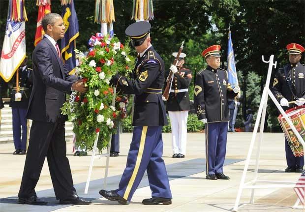 O presidente Barack Obama é ajudado a levar flores até o Túmulo dos Desconhecidos, monumento que lembra vítimas que não tiveram os corpos identificados em guerras, no Cemitério de Arlington, na Virgínia (Foto: Reuters)