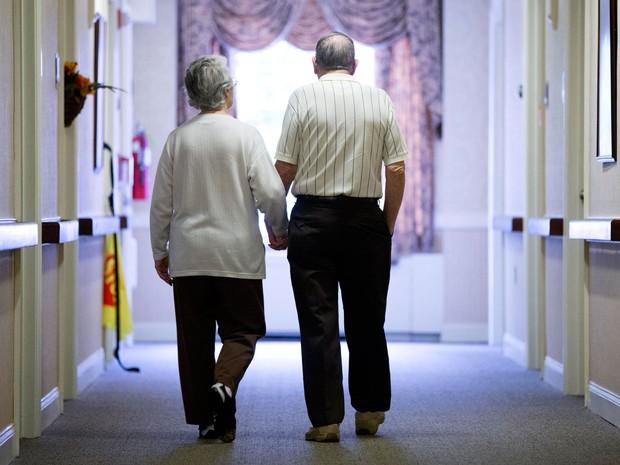 Idosa com Ahzheimer anda ao lado de seu companheiro em corredor de uma instituição americana dedicada ao atendimento desses pacientes, em foto de novembro de 2015  (Foto: AP Photo/Matt Rourke)