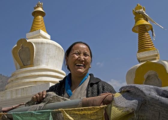 Uma senhora budista arruma as bandeiras de prece em um templo nas redondezas de Paro, no Butão  (Foto: © Haroldo Castro/ÉPOCA)