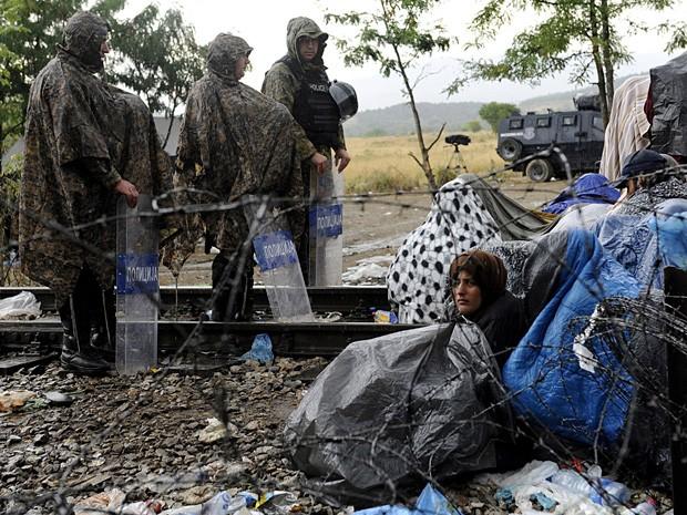 Polícia da Macedônia dica de guarda diante de imigrantes perto da passagem de fronteira com a Grécia (Foto: Alexandros Avramidis / Reuters)