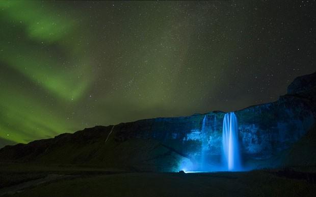 Uma noite clara criou o ambiente para esta foto da aurora boreal sobre a gigantesca cachoeira de Seljalandsfoss, na Islândia (Foto: Paul Andrew/Observatório Real de Greewich)