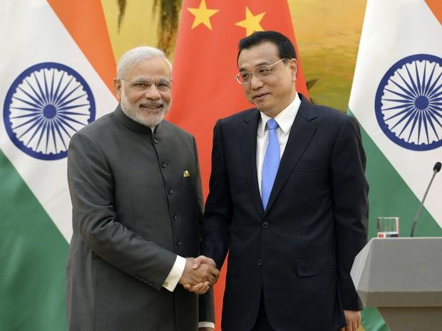Primeiro-ministro indiano Narendra Modi, à esquerda, cumprimenta o premiê chinês, Li Keqiang, durante coletiva de imprensa no Grande Salão do Povo, em Pequim, na China (Foto: Kenzaburo Fukuhara/Pool Photo/AP)