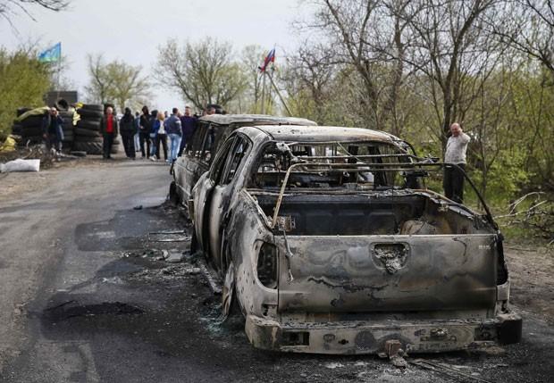 Carros queimados são vistos perto de posto de controle dominado por separatistas que foi alvo de ataque em Slaviansk, na Ucrânia, neste domingo (20) (Foto: Gleb Garanich/Reuters)