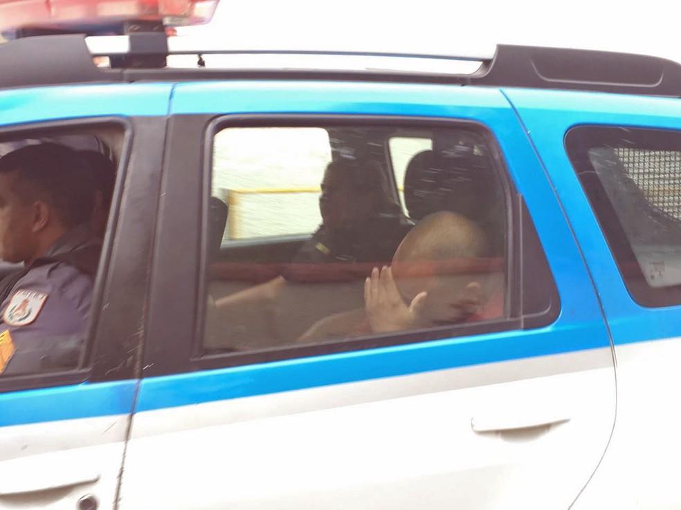 PM preso na megaoperação esconde o rosto ao ser levado por outrols policiais (Foto: Fernanda Rouvenat/G1)