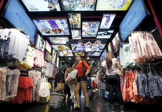 Consumidora observa roupas na loja Primark, especializada em fast fashion, roupas mais baratas e descartáveis (Foto: Divulgação)