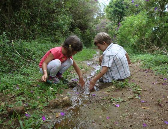 Crianças brincam com água numa área natural. Elas estão aprendendo sobre o ciclo da água, hidrologia, dinâmica de fluidos e muito mais (Foto: Lais Fleury - Divulgação Instituto Alana)