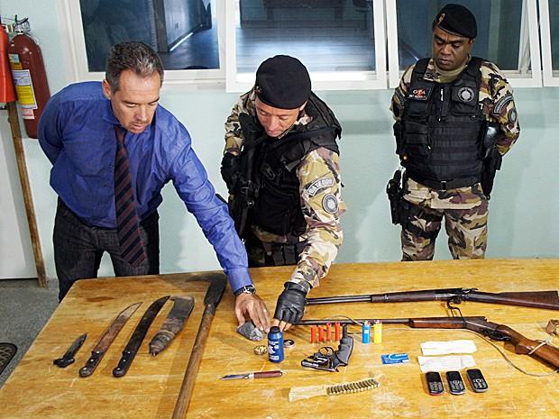Delegado-chefe da 30ª DP, Érito Cunha, e PMs do Batalhão Ambiental apresentam armas apreendidas durante operação (Foto: Ricardo Moreira / G1)