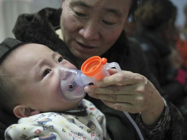 Menino faz sessão de inalação em Hospital Infantil em Pequim, na China (Foto: Reuters/China Daily)