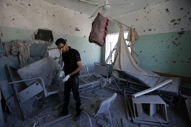Funcionário palestino inspeciona hospital que foi atingido por bombardeio nesta segunda-feira (21) na Faixa de Gaza; quatro pessoas morreram (Foto: Mohammed Abed/AFP)