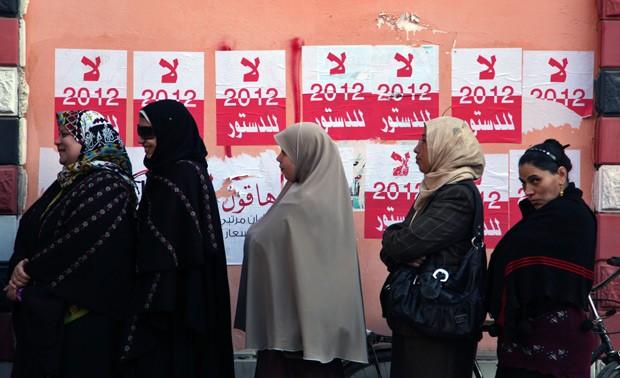 Mulheres formam fila para votar neste sábado (22) em Fayoum, em frente a cartazes da campanha do 'não' à nova Constituição do Egito (Foto: AP)