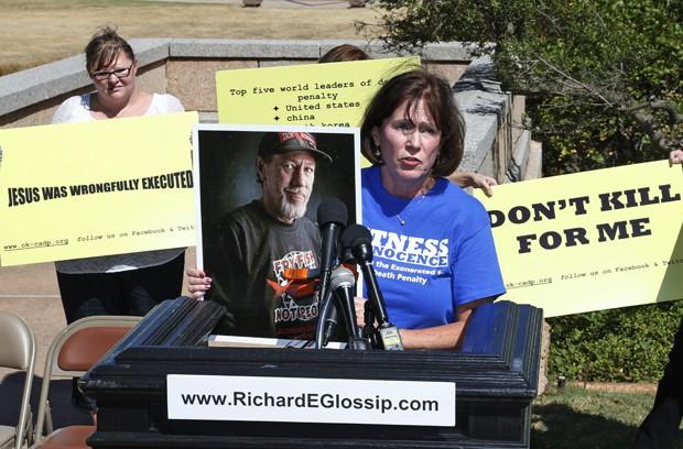 Nancy Vollertsen exibe uma foto de seu irmão, Greg Wilhoit, que passou cinco anos no corredor da morte de Oklahoma antes de ser inocentado, durante manifestação contra a execução de Richard Glossip, em Oklahoma City, na terça (15) (Foto: AP Photo/Sue Ogrocki)