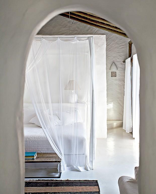 Com dossel, a cama traz enxoval branco e mosquiteiro feito por artesãs baianas. Calçadeira da Etna (Foto: Marco Antonio/ Editora Globo)