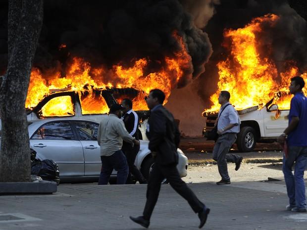 Carros foram incendiados durante protesto (Foto: Leo Ramirez/AFP)