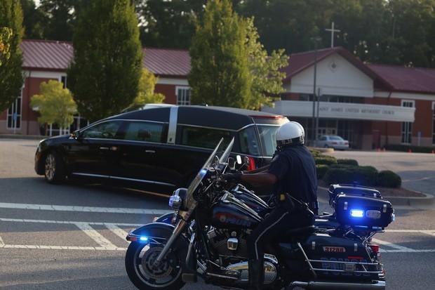 Carro funerário com o caixão de Bobbi Kristina é escoltado por policial (Foto: AFP)