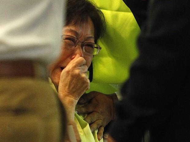 Mulher chora ao ver o nome da filha em lista de passageiros de avião que caiu na Ucrânia (Foto: Reuters)