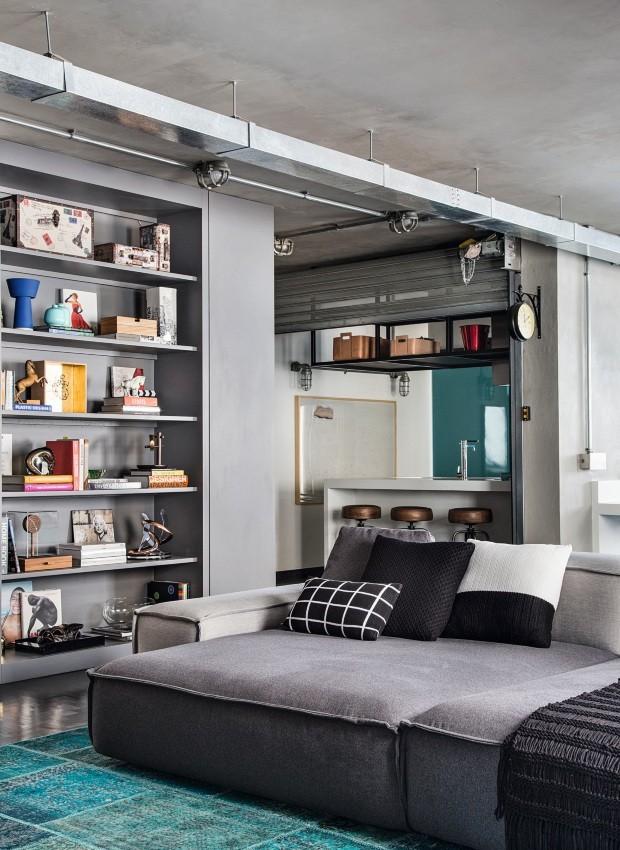 Sala de TV. Com almofadas da Codex Home, o grande sofá, desenhado pelos arquitetos e executado pela Treuni III, traz conforto ao espaço, que tem estante embutida. O tapete é da By Kamy (Foto: Denilson Machado / MCA Estúdio / Divulgação)