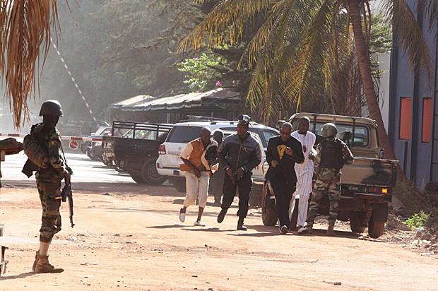 Malineses fogem de área cercada pelo exército ao redor do hotel Radisson Blu (Foto: Harouna Traore/AP)