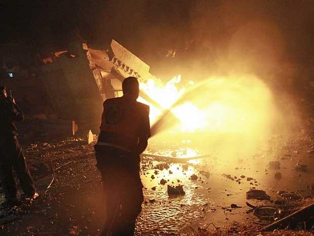 Bombeiros tentam extinguir fogo em um prédio atingido por bombardeio israelense na Faixa de Gaza. (Foto: Adel Hana / AP Photo)