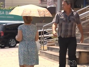 Enquanto calor continua, população usa guarda-chuvas para se proteger do sol (Foto: Reprodução/TV Anhanguera)