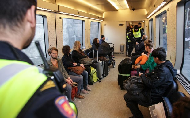 Policiais suecos fazem controle de passageiros em trem na fronteira com a Dinamarca nesta quinta-feira (12) (Foto: Stig Ake Jonsson/TT via AP)