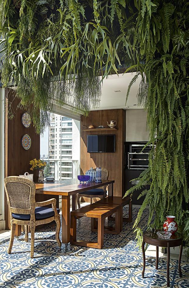O jardim vertical rouba a atenção nesta varanda projetada pela arquiteta Selma de Sá Moreira. A vegetação se soma ao azul e à madeira, que dão ar de casa ao apartamento. O piso é de ladrilho hidráulico (Foto: Edu Castello/Casa e Jardim)