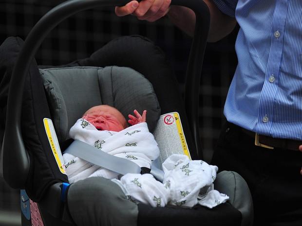 23/7 - William carrega seu filho para dentro do carro ao deixar o hospital (Foto: Carl Court/AFP)