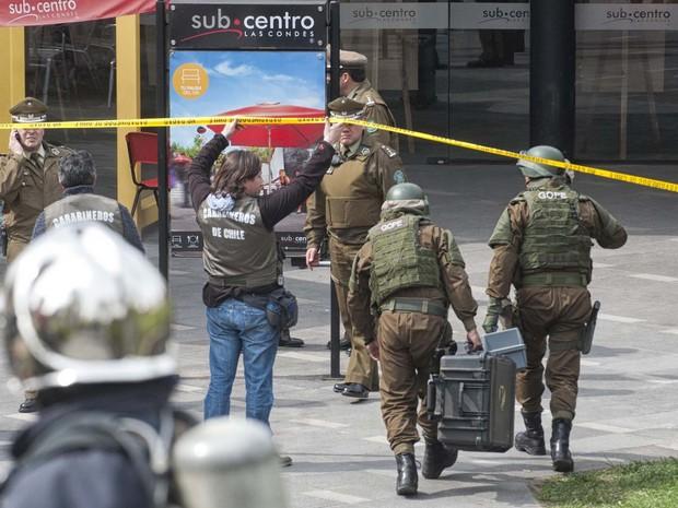 Policiais do departamento anti-bombas chegam a estação de metrô Escuella Militar, em Santiago, no Chile. Pelo menos nove pessoas ficaram feridas em ato classificado como 'terrorista' pelo governo do país (Foto: Sergio Pina/AFP)