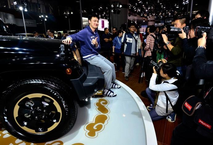 Nadador chinês Zhang Lin posa ao lado de carros de luxo durante a exposição em Guangzhou (Foto: Agência Reuters)