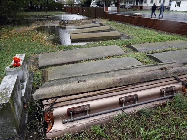 30 de outubro - Caixão saiu parcialmente de sua cova no cemitério de Crisfield, em Maryland, devido à força da supertempestade Sandy. Centenas de pessoas ficaram desabrigadas na cidade devido às enchentes (Foto: Alex Brandon/AP)