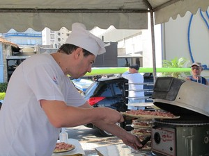 Pizzaiolo coloca a pizza no forno, em frente a praia (Foto: Mariane Rossi/G1)
