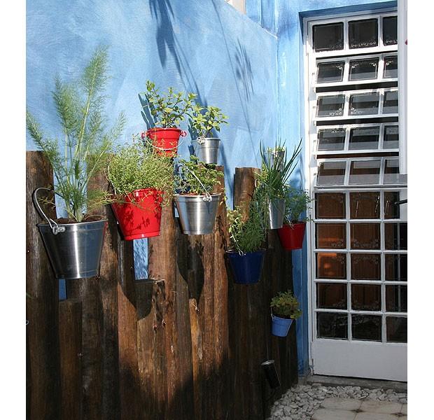 No corredor, as toras de eucalipto fixadas na parede sustentam minivasos de alumínio com ervas e temperos. Leves, esses vasos são ideais para serem pendurados. Na composição, aparecem no tom original ou pintados de vermelho e azul (Foto: Evelyn Müller/Editora Globo)