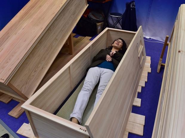 Mulher testa caixão durante feira da indústria funerária (Foto: Yoshikazu Tsuno/AFP)