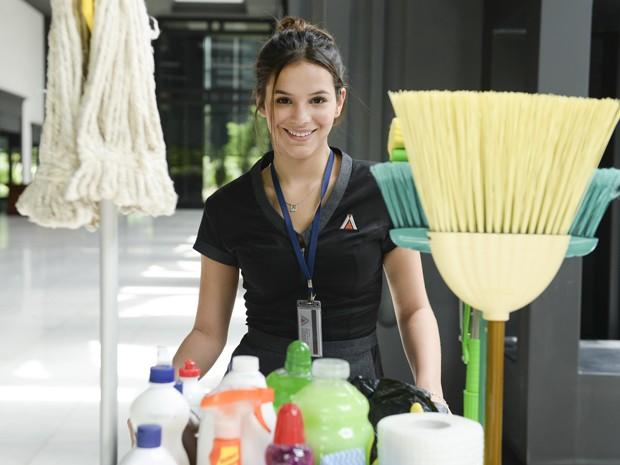 Esbanjando sorriso e disposição, Bruna empurra um carrinho de limpeza (Foto: Globo/Zé Paulo Cardeal)
