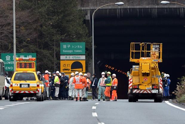 Policiais e bombeiros se concentram na entrada do túnel de Sasago neste domingo (2) (Foto: AP) (Foto: AFP)