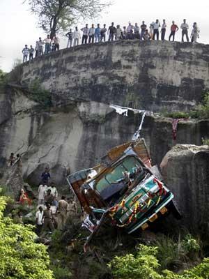 Policiais inspecionam destroços de caminhão que saiu da pista e despencou de ribanceira na Caxemira. (Foto: Channi Anand / AP Photo)