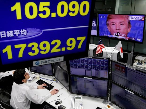 Funcionário de uma empresa de operações de câmbio trabalha diante de uma TV que mostra Donald Trump, nesta quarta-feira (9), em Tóquio (Foto: Toru Hanai/Reuters)
