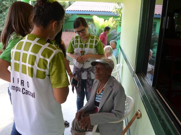 Estudantes e idosos dividiram experiências durante a entrega dos alimentos (Foto: Rogério Aderbal/G1)