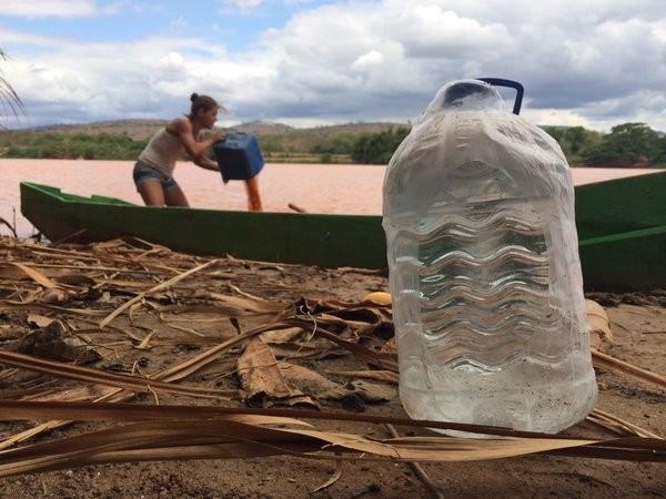A agricultura Vera Krause tira água enlameada do Rio Doce do barco; à frente, água mineral que agora abastece a casa (Foto: Alexandre Nascimento/G1)