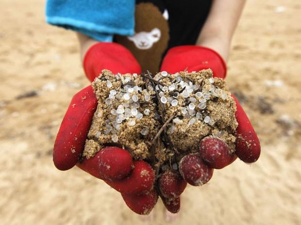 Voluntária mostra areia misturada a bolinhas de plástico em praia de Hong Kong; governo estima que 150 toneladas foram derramadas no litoral (Foto: Tyrone Siu/Reuters )
