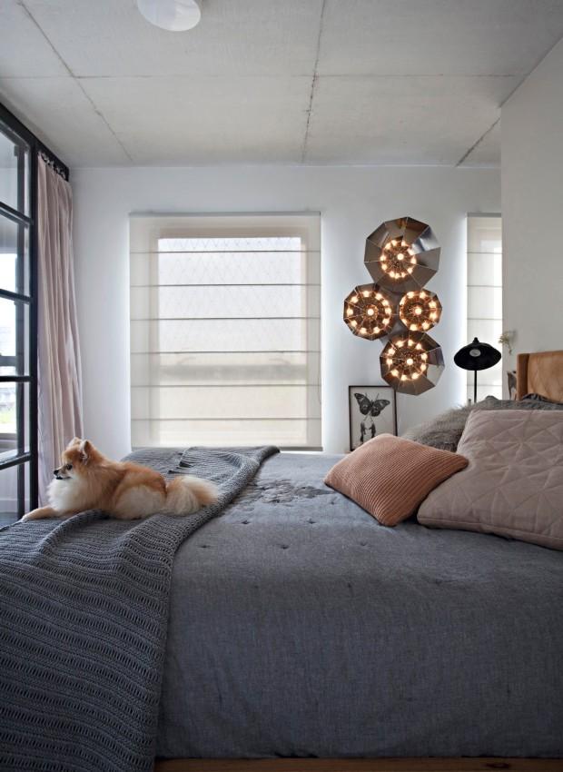 Detalhes. A cadela Amelie guarda a cama da dona. Atrás, na parede, a luminária escultórica da Prototype (Foto: Marco Antonio / Editora Globo)
