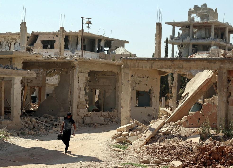Membro do Exército Livre da Síria, grupo opositor ao governo de Bashar al-Assad, caminha neste domingo (9) em meio a prédios danificados em parte da cidade de Daraa tomada pelos rebeldes  (Foto: REUTERS/Alaa Al-Faqir)