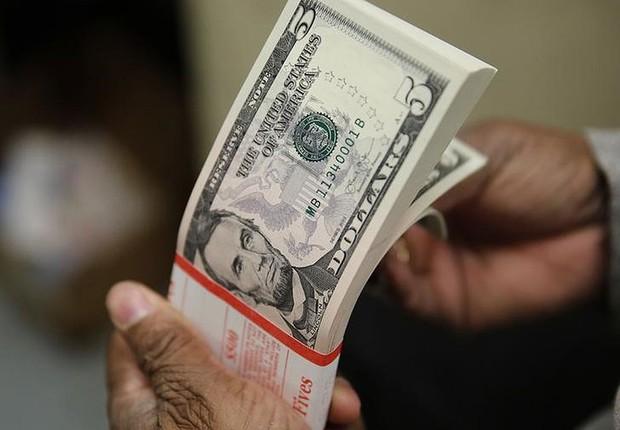 Pacote de notas de cinco dólares dos Estados Unidos passam por inspeção em Washington, nos EUA (Foto: Gary Cameron/Arquivo/Reuters)